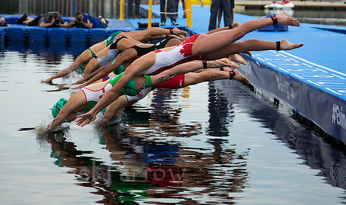 26 JUL 2014 - GLASGOW, GBR - Kirsten Sweetland (CAN) (centre in red and white) from Canada along with the other competitors dive into the water at the start of the swim at the 2014 Commonwealth Games Mixed Relay triathlon in Strathclyde Country Park, in Glasgow, Scotland  (PHOTO COPYRIGHT &copy; 2014 NIGEL FARROW, ALL RIGHTS RESERVED<br /> *******************************<br /> COMMONWEALTH GAMES <br /> FEDERATION USAGE <br /> RULES APPLY<br /> *******************************