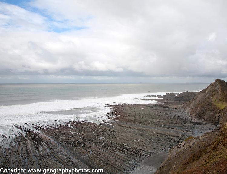 Rocky wave cut platform erosional landforms with ridges formed by eroded tilted strata at Hartland Quay, north Devon, England