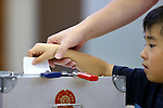 A child casts a ballot for his parents in Japan's upper house election at a polling station in Tokyo, Japan on July 10, 2016. (Photo by AFLO)