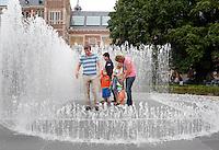 Familie vermaakt zich in de fontein van het Rijksmuseum in Amsterdam