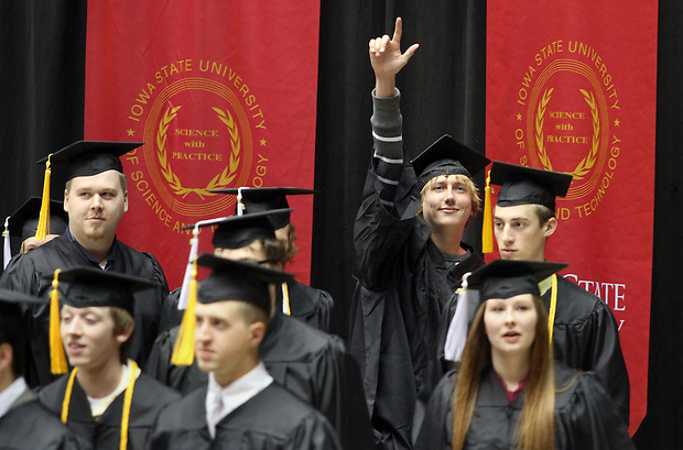 Benji Lamfers of Sioux Center signals to his family while entering Hilton Coliseum with his college of liberal arts and sciences classmates during Iowa State University's spring 2010 commencement ceremony Hilton Coliseum in Ames.  He is graduating with a major on computer science.