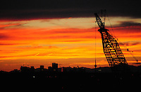 Tempe, Arizona. A majestic sunset creates a dramatic silhouette of one of two giant cranes being used in the construction site. This view also offers a view of the Downtown Phoenix skyline in the background. The artificial lake is a reservoir on a segment of the currently dry riverbed of the Salt River. The new dam will be a cost-effective solution expected to last for decades. The construction is called Town Lake Western Dam Replacement Project. Photo by Eduardo Barraza © 2015