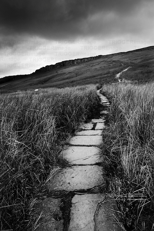 A stone path leading off into the distance on moorland in winter. Hooks Car, Peak District, Derbyshire, England