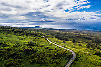 Aerial view of a winding road through Ulupalakua Ranch, Maui, with Kaho'olawe in the distance.