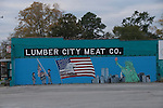 911 mural with flags, firemen, Statue of Liberty, World Trade Towers painted on side of the Lumber City Meat Market