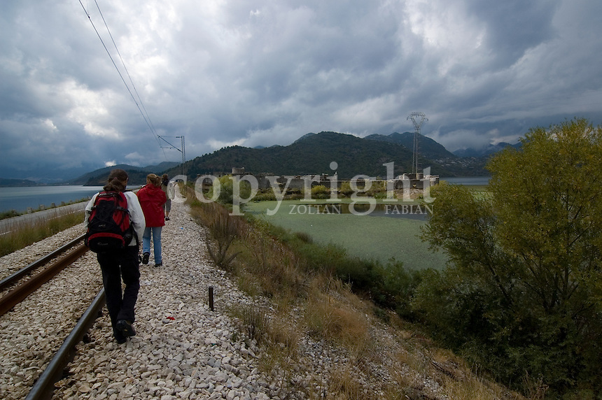 Three young people walk along the tracks next to the Unesco protected Skadar lake in Montenegro