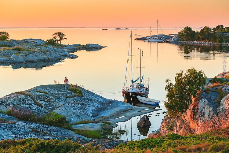 Man på klippa vid sin förtöjda segelbåt vid en spegelblank fjärd vid Kallskär i Stockholms ytterskärgård,