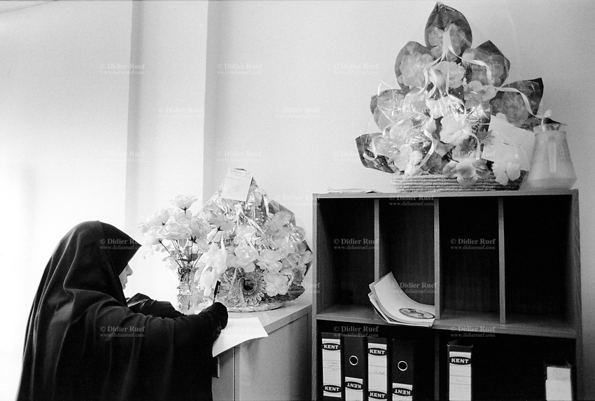 Iraq. Basra. The secretary of mayor Basan Wael Al Allatef writes a note on an office furniture. The woman wears the abaya and the hidjab on her head to cover her hair. The abaya, sometimes also called aba, is a simple, loose over-garment, essentially a robe-like dress, worn by some women in parts of the Islamic world. Traditional abaya are black and may be either a large square of fabric draped from the shoulders or head or a long caftan. The abaya covers the whole body except the face, feet, and hands. The word hijab (or hidjab) refers to both the veil covering the head and traditionally worn by muslim women (Islamic headscarf), but also the  modest muslim styles of dress in general. Basra ( in arabic Al Basrah) is the capital of Basra Governorate in southern Iraq. 01.03.04 © 2004 Didier Ruef