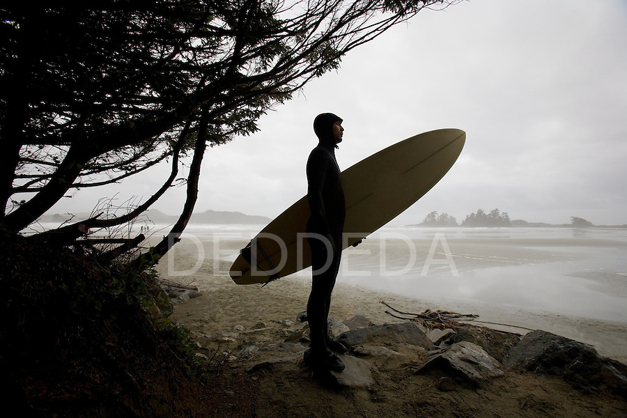A surfer looks out over Chesterman's Beach, a popular Canadian surf destination in Tofino, BC, British Columbia, Canada.
