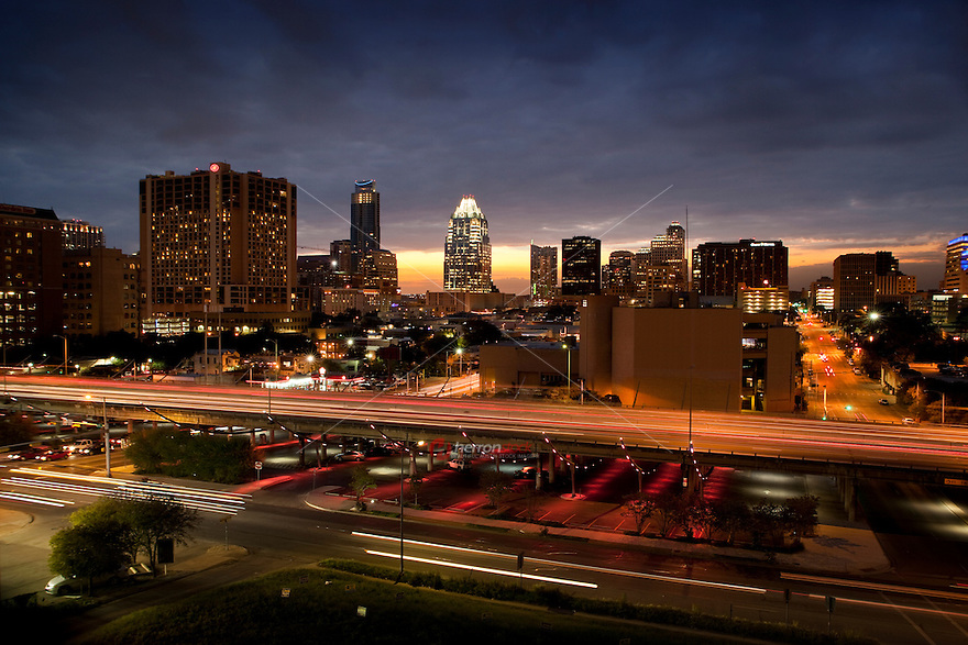 Sunset falls on the downtown Austin Skyline as the I-35 Makeover Project Parking garage performs its colored light show in red