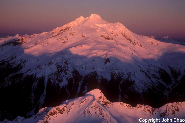 Aerial of Glacier & Skullcap Peaks at sunset with alpenglow lighting, North Cascade Mountains, Washington State.