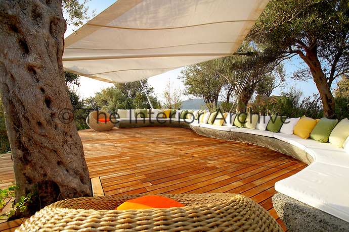 An outdoor seating area with shade provided by a canopy above. A curving stone seat with green and yellow cushions is set on a raised decked terrace.