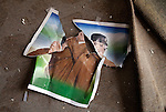 Anti-Gaddafi fighters tore up images of Col. Muammar Gaddafi found in homes, some destroyed by shelling, in the Seven Hundred neighborhood of Sirte, Libya, Oct. 7, 2011. Revolutionaries pressed in to Col. Muammar Gaddafi's hometown, encountering fierce resistance snipers, rocket-propelled grenades, and mortars.