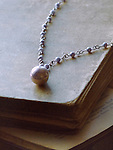An old large violet pearl necklace laid on antique books.