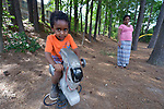 Three-year old Youel rides a play horse as his mother, Tirhas Drar Brehane, looks on in a playground in Durham, North Carolina. <br /> <br /> Refugees from Eritrea, the boy and his mother were resettled in Durham by Church World Service, which resettles refugees in North Carolina and throughout the United States.<br /> <br /> <br /> Photo by Paul Jeffrey for Church World Service.