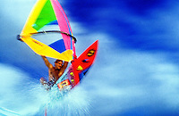 A colorful windsurfer sails through a sea of blue and white froth.