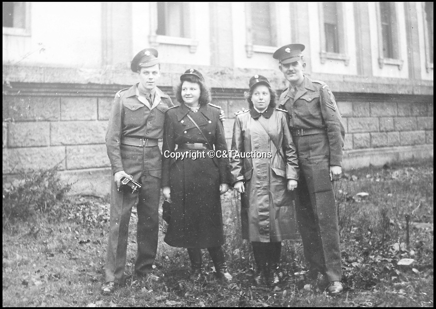 BNPS.co.uk (01202 558833)Pic: C&TAuctions/BNPS<br /> <br /> The Guardsman (L) with Russian female soldiers in Berlin.<br /> <br /> Reich in Ruins - An incredible album of unseen photographs from Hitler's devastated Reich Chancellery, taken one of the first British soldiers into a devastated Berlin has come to light.<br /> <br /> The photo album was compiled by an elite soldier of the 1st Battalion Grenadier Guards that rolled into Berlin on 4th of July 1945. <br /> <br /> The photos show the inside of Hitler's spacious private office from behind his imposing desk and the conference hall where the Nazi high command met to plot their next move.<br /> <br /> By the time the unknown Guardsman set foot in the chancellery, its lavish marble interior had been battered by the Red Army assault and only a pile of rubble remained.<br /> <br /> The soldier composed an album of his own photographs alongside Nazi publicity postcards from the heyday of the Third Reich.