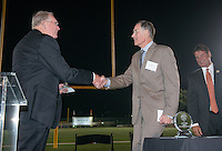 John McGrath '63 accepts the Athletics Hall of Fame award from Glen Johnson '60. Alumni, family, staff and students at the Occidental College Athletics Hall of Fame event, part of Homecoming weekend, Oct. 24, 2014 on Patterson Field. (Photo by Marc Campos, Occidental College Photographer)