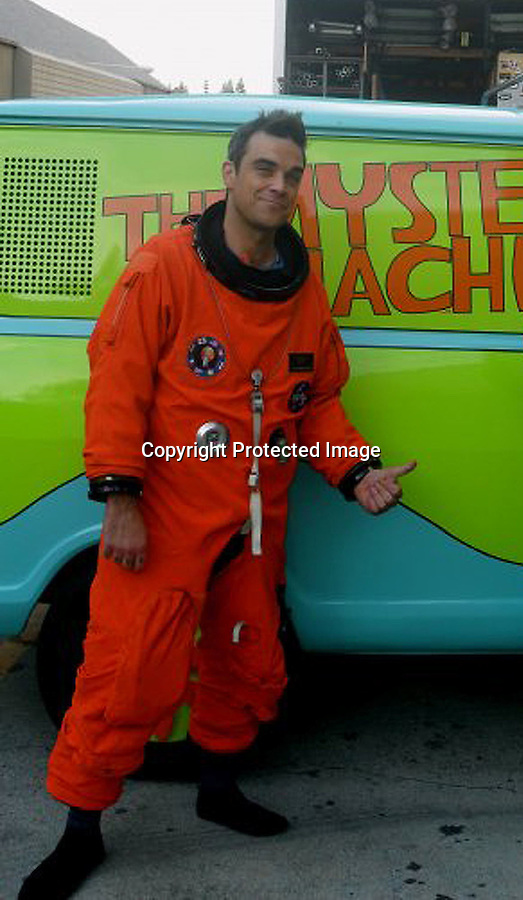 .3-12-2010.Exclusive...Robbie Williams dressed up in an orange astronaut suit at Universal Studios Hollywood for a music video he was filming. Robbie stopped to take a picture next to the Scooby Doo Mystery Machine van. ...AbilityFilms@yahoo.com.805-427-3519.www.AbilityFilms.com.