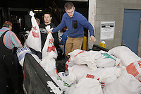 Wednesday, February 13, 2013.   Musher Mike Suprenant's  handler, Adam Lang passes a truck-bed full of food bags to volunteers  at Airland Transport in Anchorage during the musher food drop day.  Iditarod 2013