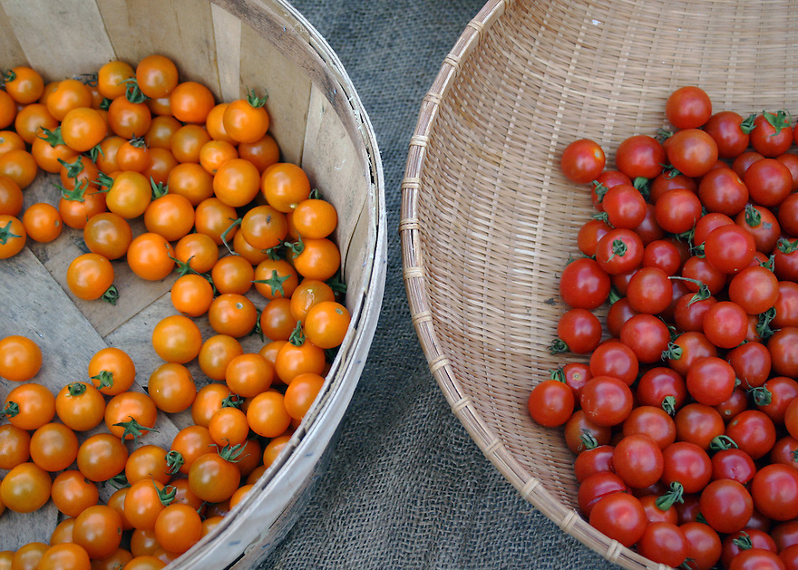 Two baskets of fresh cherry tomatoes at market stand