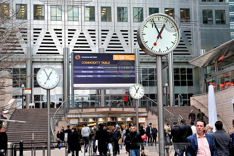 Clocks in Canary Wharf show that it is four minutes to one, with Brent Crude, Gold and Colombian coffee prices displayed on a Commodity Table outside the Thomson Reuters building in London's Docklands.