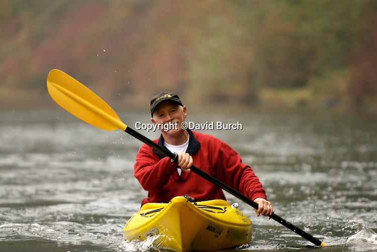 Mature man kayaking on river