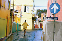 Antigua, 2004 - In the island capitol of St. John a barefoot man casually walks down rain wet High street from the intersection with Soul Alley.