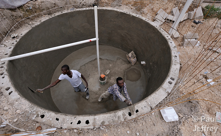 Richardson Henry (right) and another worker smooth fresh cement in a biodigester being built at the Lycee Petion in Port-au-Prince, Haiti. One of four pilot projects being built in the Belair neighborhood of the earthquake-ravaged city, the tank will use human waste from students at the school, converting it into cooking gas. The project is funded by International Orthodox Christian Charities and carried out by VivaRio, a Brazilian NGO that has been working in Belair for years.