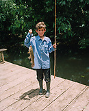 PERU, Amazon Rainforest, South America, Latin America, portrait of a Asa with a fish he just caught from the Tambopata River.