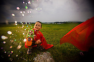 A boy wearing a cape fires his toy bubble gun at the camera as his friend runs away.