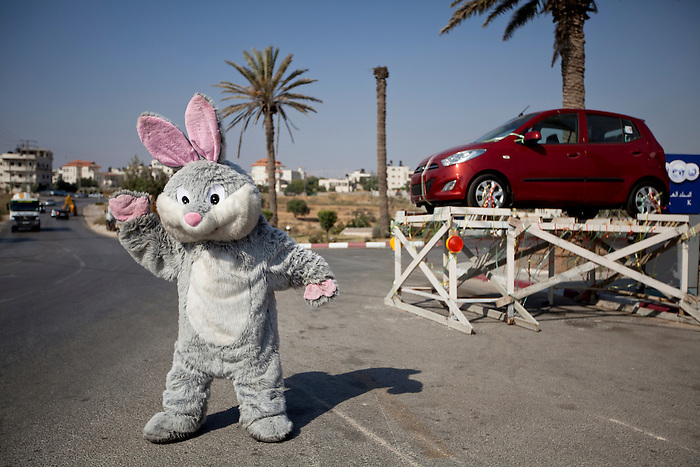 June 2012, Nearby Ramallah, West Bank. Advertising for a lottery in a Gas station, with a car as a first prize, suburb of Ramallah. Every time they spend 50 Shekel in the gas station, the customers get a ticket for the lottery. In the Rabbit costume, a child of 14 years old is sweating to attract the clients. Ziyad Taleb, the owner of the gas station and 1948 refugee, discovered this marketing technique in Thailand during a holiday trip, and found the idea very clever.