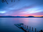 Idaho,North, Coeur d'Alene. Pink afterglow of a summer sunset over Lake Coeur d'Alene, with canoe on dock.