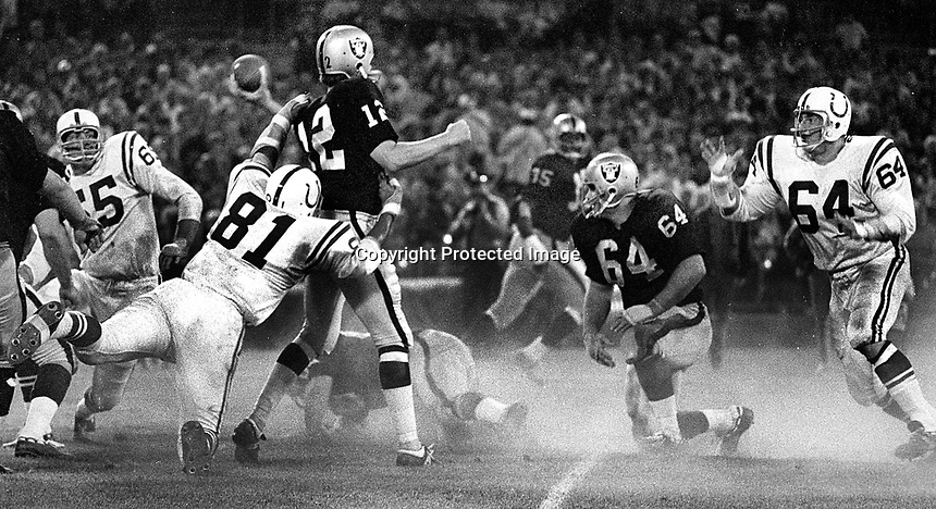 Raiders Ken Stabler passing against the Baltimore Colts #81 Ordell Braase, and #64 Sid Williams..(1969-1970 photo/Ron Riesterer)