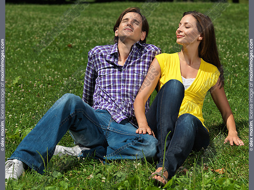 Young happy couple in their early thirties sitting on grass in a park