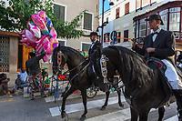 "Spain. Balearic Islands. Minorca (Menorca). Mahon. Two horsemen during the ""Festes de la Mare de Déu de Gràcia"" which is a traditional summer festival. The Menorquín is a breed of horse indigenous to the island and is closely associated with the doma menorquina style of riding. The riders wear black and white and most of their horses (adorned with ribbons and multi-coloured rosettes) are of the highly-considered Menorcan breed. The riders and their horses parade through the streets, and these magnificent and remarkably calm horses rear up on their hind-legs to the delight of the crowd. Horses and riders are at the centre of local fiesta celebrations, in a tradition that may go back to the 14th century and incorporate elements of Christian, pagan and Moorish ritual. Some 150 riders participate in the festival in Mahón. A group of african men, all immigrants either seating or standing on the sidewalk, sell inflated plastic balloons and diverse toys on a market stall in the street. Maó (in Catalan) and Mahón (in Spanish), written in English as Mahon, is a municipality, the capital city of the island of Menorca, and seat of the Island Council of Menorca. The city is located on the eastern coast of the island, which is part of the autonomous community of the Balearic. In Spain, an autonomous community is a first-level political and administrative division, created in accordance with the Spanish constitution of 1978, with the aim of guaranteeing limited autonomy of the nationalities and regions that make up Spain. 7.09.2019 © 2019 Didier Ruef"