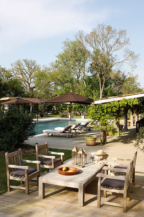 The covered terrace is situated next to the outdoor swiming pool and the teak garden furniture is by Sarah Lavoine