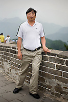 Zhangyongxue, a teacher, age 41, poses for a portrait in Badaling. Response to 'What does China mean to you?': 'To me, as I stand on top of the Great Wall, China is in the middle of digging itself out.'  Response to 'What is China's role in the future?': 'In the future China will certainly only get stronger as it goes forward.'