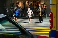 HONG KONG - APRIL 13: Three people wait to cross the street in Central business district, on April 13, in Hong Kong. (Photo by Lucas Schifres/Pictobank)