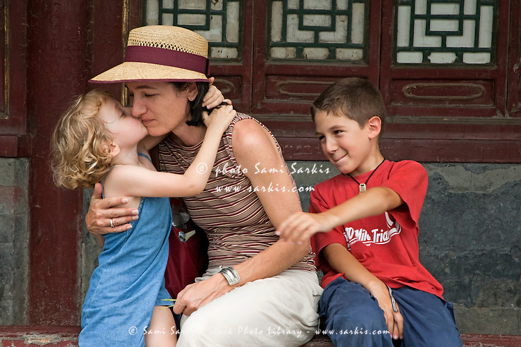 Mother shares a tender moment with her two children while taking a break in Behai Park, Beijing, China.