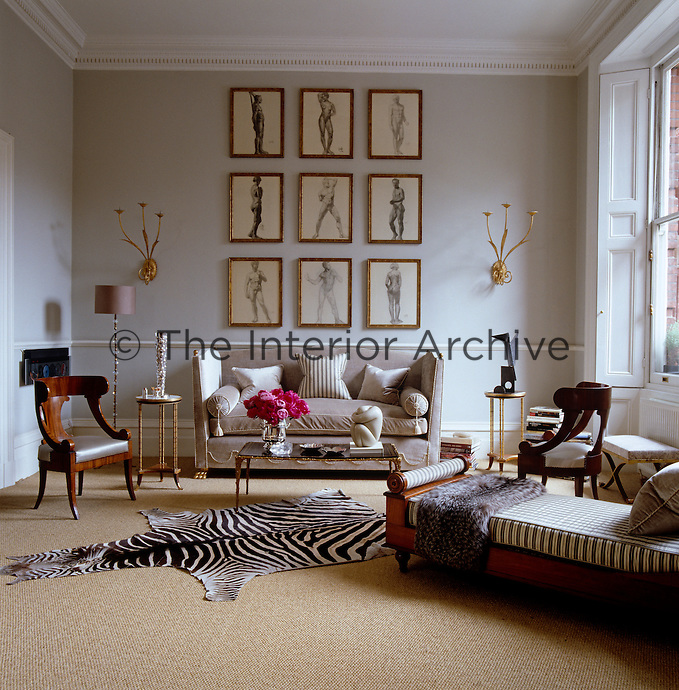 The ticking covering the cushion of the chaise-longue in the living room echoes the colour and pattern of the zebra-skin rug