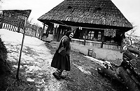 ROMANIA / Maramures / Valeni / March 2003..An old woman returns to her traditional wooden house after chopping firewood. This style of home, of which there are several variations, is specific to the Maramures region...© Davin Ellicson / Anzenberger..