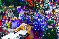 November 27, 2015, Yiwu China - A vendor sits at a desk inside her booth where plastic Christmas trees are displayed in the Festival Arts section of the Yiwu International Trade Market. Yiwu International Trade Market is the world's largest whole sale market for small commodities. Christmas decorations are available for bulk purchase all the year round.Photo by Dave Tacon / Sinopix