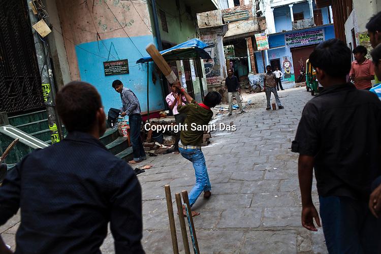 young men play cricket in the narrow alleys in the ancient city of Varanasi in Uttar Pradesh, India. Photograph: Sanjit Das/Panos