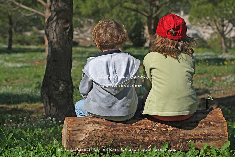 Two little girls sitting on a tree trunk in the forest.