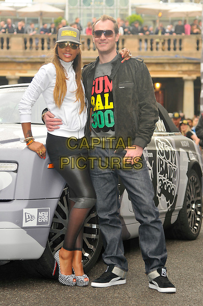 EVE (Eve Jihan Jeffers) & MAXIMILLION COOPER.The start of Gumball 3000, Covent Garden, London, England. .May 26th, 2011.full length black leather sheer leggings white top baseball cap hat sunglasses shades platform shoes pep toe jacket jeans denim couple.CAP/CAS.©Bob Cass/Capital Pictures.