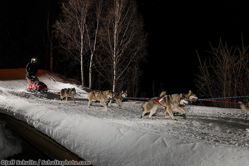 Mike Ellis drives his dog team across the bridge as he leaves the Takotna checkpoint, on Wednesday, March 5, during the Iditarod Sled Dog Race 2014.<br /> <br /> PHOTO (c) BY JEFF SCHULTZ/IditarodPhotos.com -- REPRODUCTION PROHIBITED WITHOUT PERMISSION