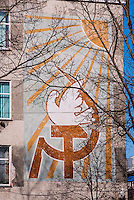 Russia, Sakhalin, Yuzhno-Sakhalinsk. The old Hammer and sickle symbol painted on a wall.