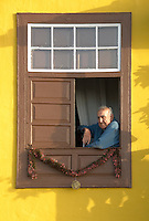 Spain, Canary Islands, La Palma, Tazacorte: residential building, man sitting at open window