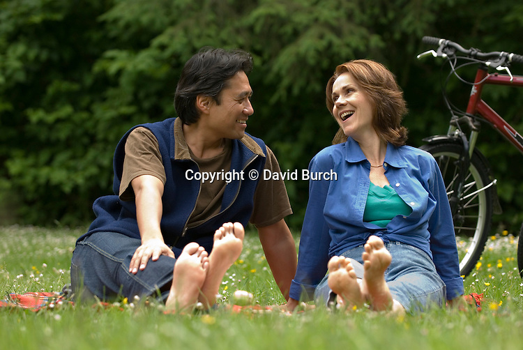 Couple barefoot, laughing in meadow with bikes